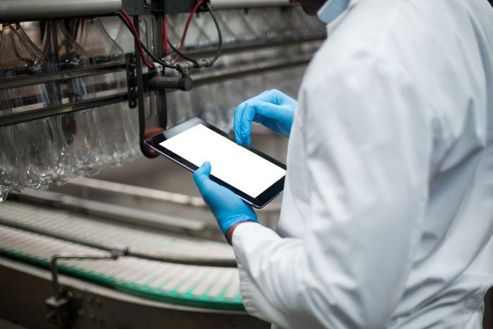 Trabajador en una fábrica utiliza una tablet.
