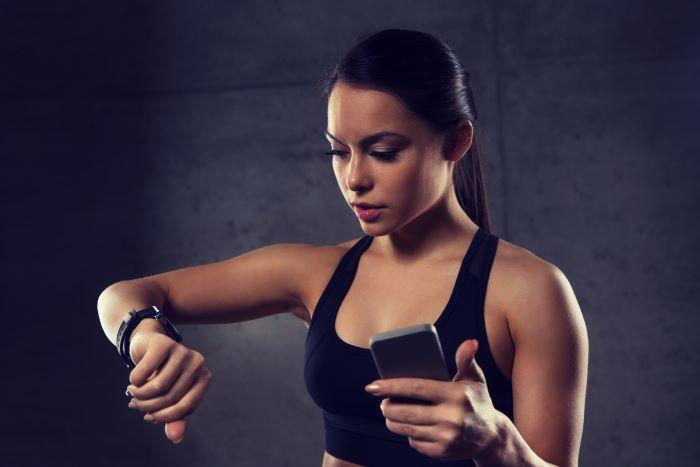 Mujer utiliza sus dispositivos móviles para hacer ejercicios.